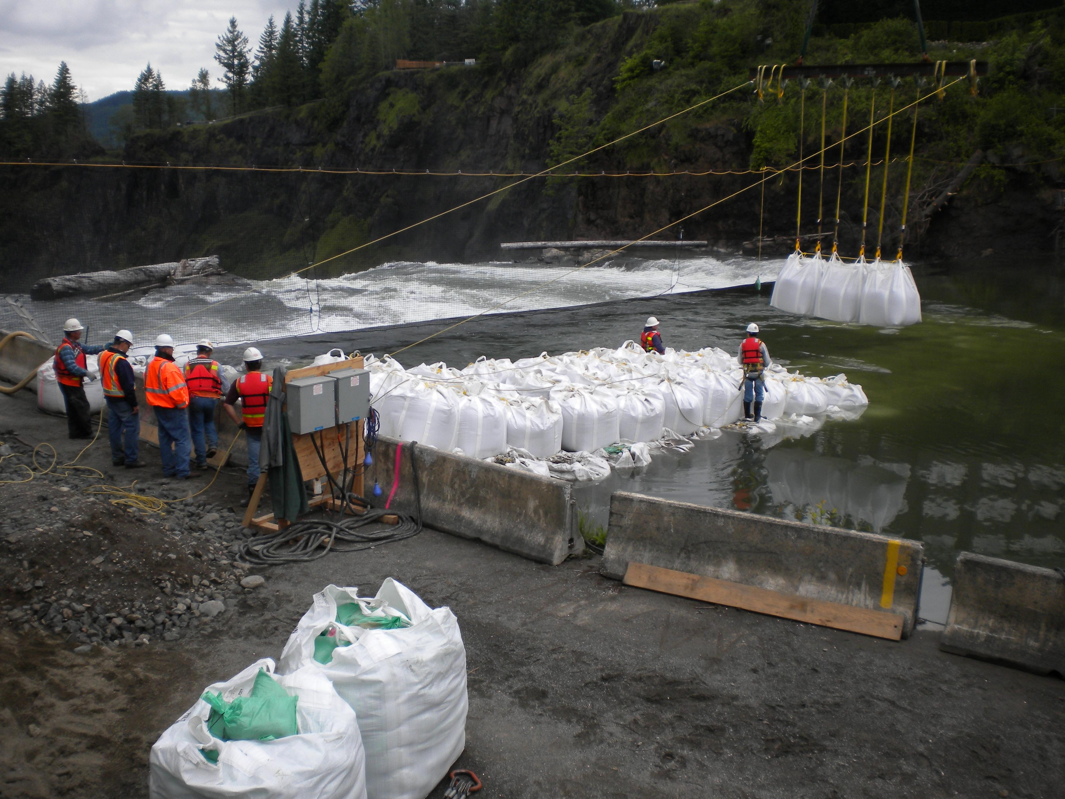Engineers work to build a coffer dam using bulk bags.