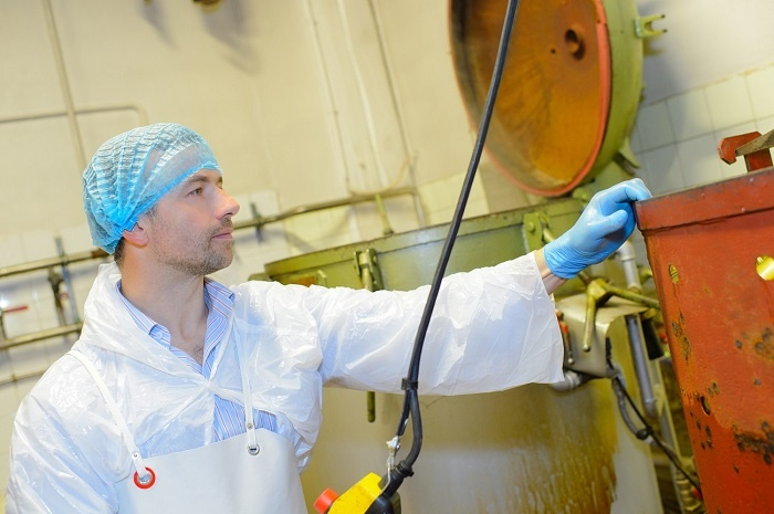 A man with a hairnet checks the levels of a liquid in a food facility.