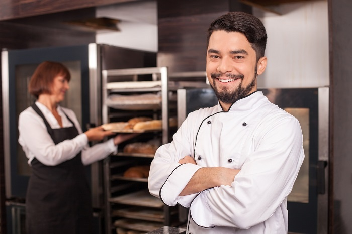 A baker stands proudly in front a tray of freshly baked bread.