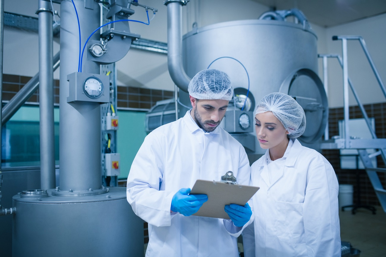 Two food production workers in full smocks read a factory check list.