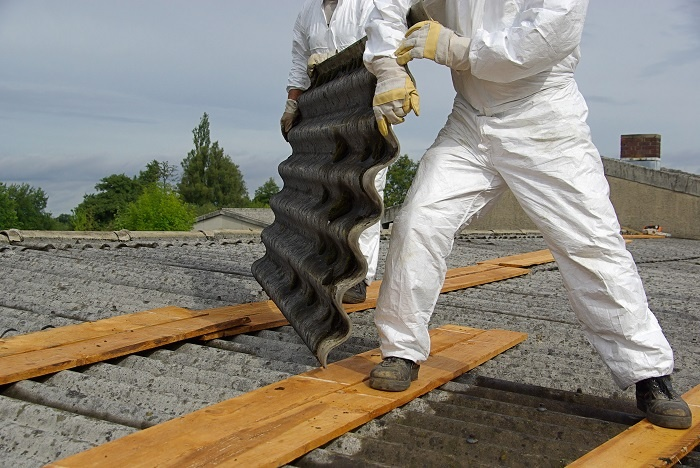 Workers in HazMat suits remove asbestos panels.