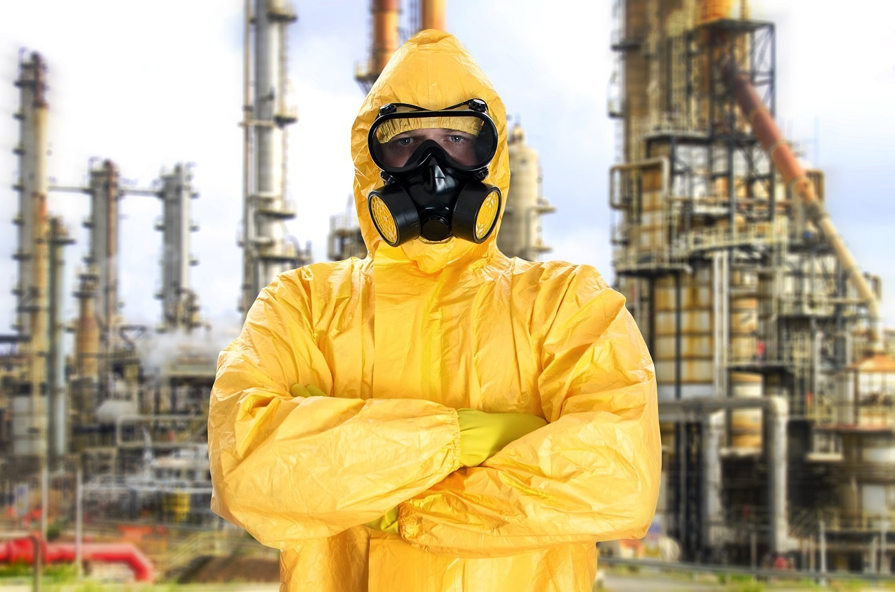 Worker in a HazMat suit getting ready to remediate a contaminated site.