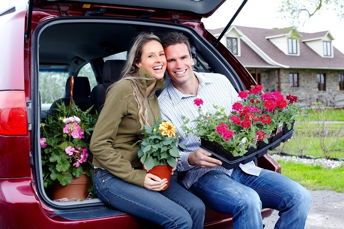 A happy young couple posing with flowers they will plant at home.