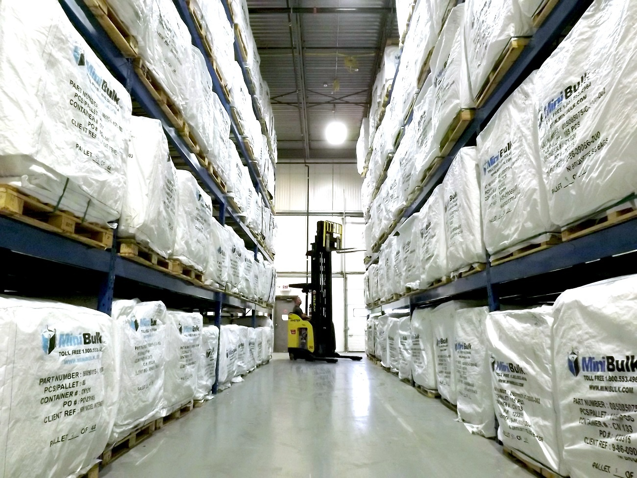 A forklift prepares to fetch bulk bags from the top of warehouse racking.