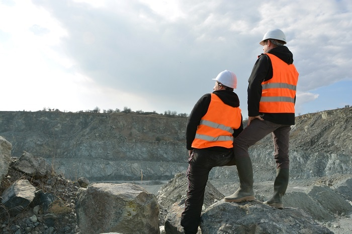 Two men survey the landscape of an open-pit mine.