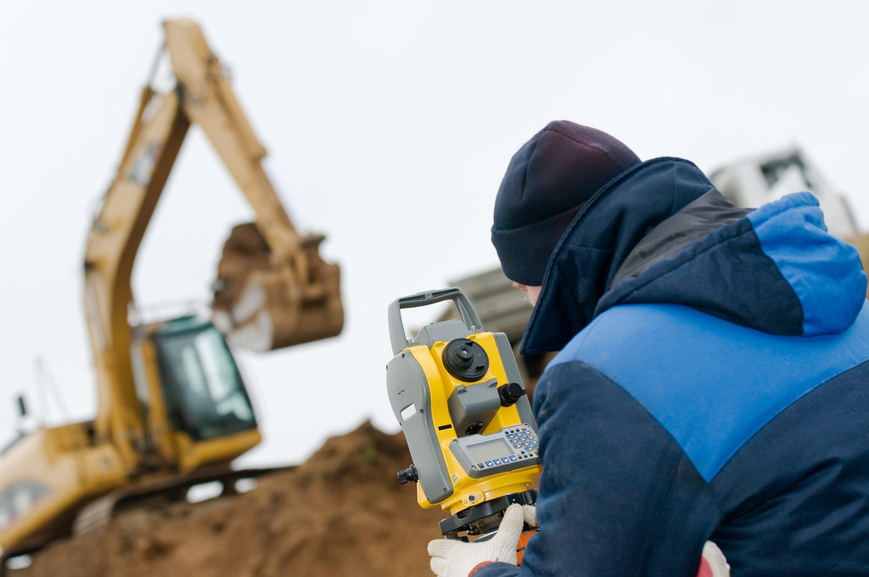 A surveyor checks the progress of a track hoe moving earth.