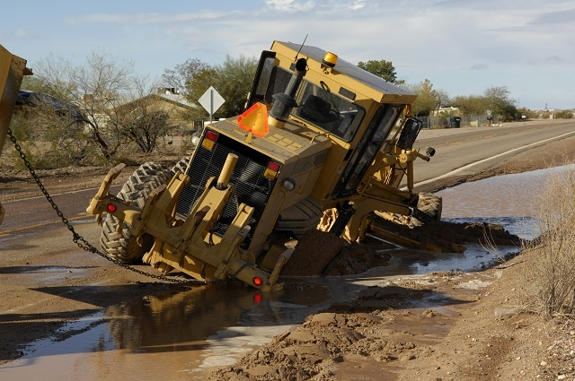 Heavy equipment getting towed out of the mud